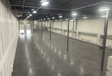 Image depicts a recently completed concrete polishing project done by Polished Floors in a warehouse.