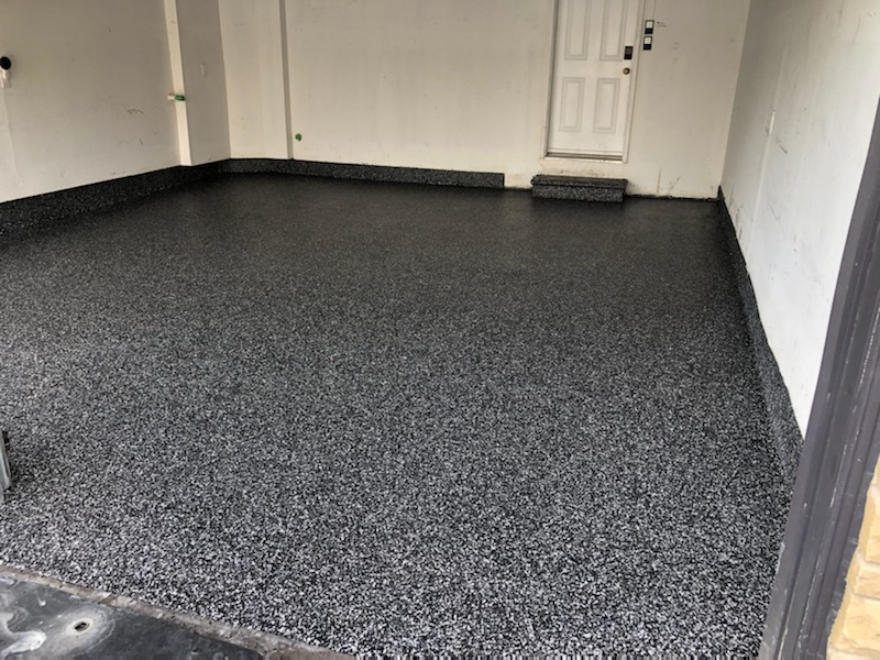 Image depicts a new garage epoxy floor in a residential garage.