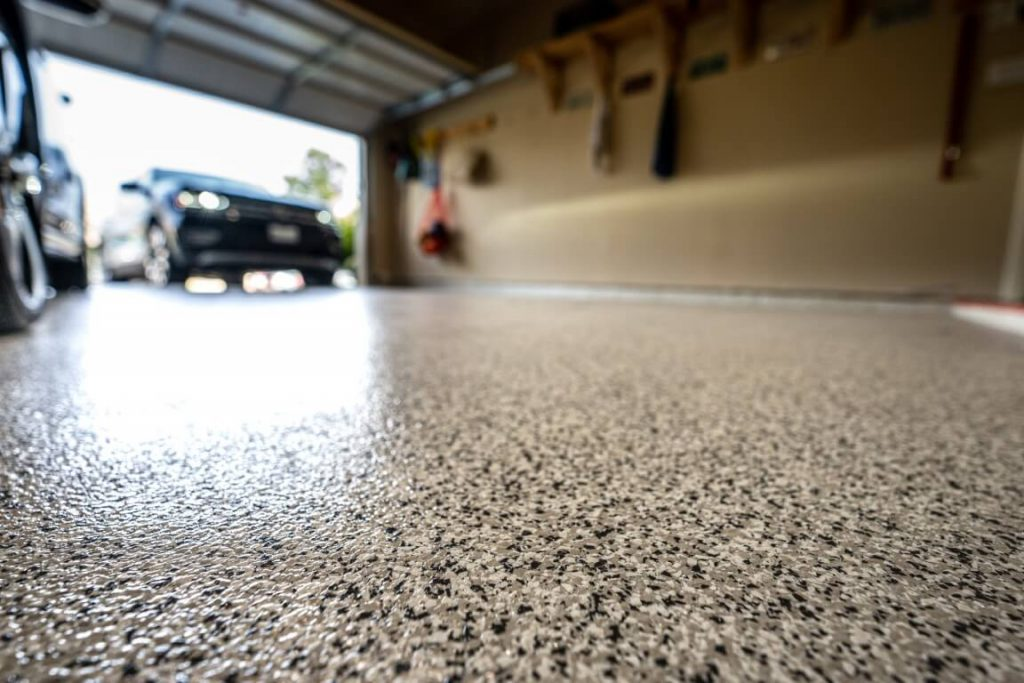 Image depicts a garage epoxy flooring project by Polished Floors.