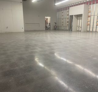 Image depicts a warehouse floor in Milton with concrete floors that have been polished.