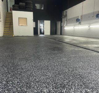 Image depicts flake epoxy flooring installed in a car detailing shop.