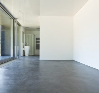 Image depicts a modern hotel room with recently polished concrete floors.